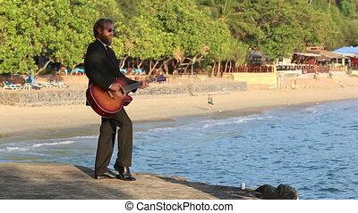 guitarist in black suit plays against beach