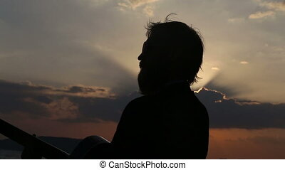 silhouette of guitarist at backlight against sunset