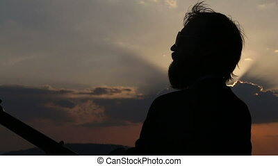silhouette of guitarist at backlight at sunset he goes out