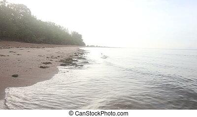 light waves beat into sand sea bank at dawn
