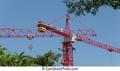 crane towering above builders of house - panorama of crane...