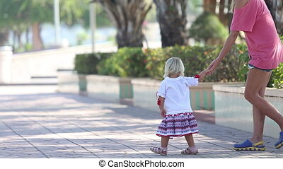 blonde girl in Ukrainian blouse leads mother away by hand
