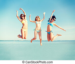 girls jumping on the beach - summer holidays and vacation -...