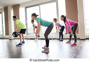 group of people exercising with barbell in gym - fitness,...