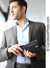 Money - Man in suit holds in hand wallet