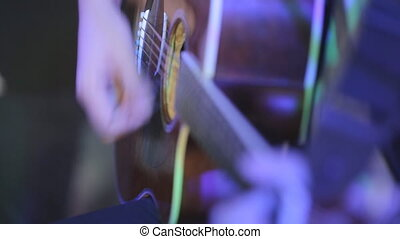 Close-up of the man playing the quitar in the lights - The...