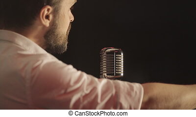 Love song in the night club of the sexy man with the beard in the retro style microphone