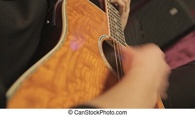 Close-up playing of the classic guitar in the night club