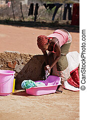 washing clothes - doing laundry, young African woman in the...
