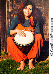 Young barefoot lady drummer playing on her djembe drum on...