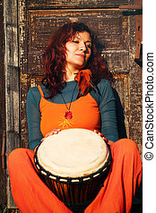 Young lady drummer with her djembe drum on rustic wooden...