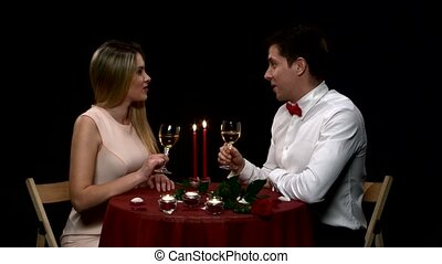 Romantic couple having dinner, clinking glasses. Close up -...
