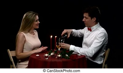 Romantic couple having dinner, clinking glasses. Close up