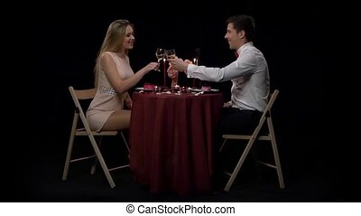 Romantic couple having dinner, clinking glasses. Slow motion