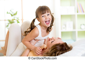 Happy mother and her kid tickle, play and laugh in bed -...