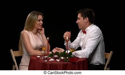 Portrait of beautiful couple enjoying each other's company in a romantic dinner. Close up. Slow motion