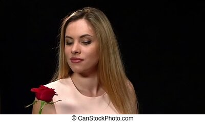 Close up of woman sniffing red rose with closed eyes isolated on black background. Close up, Slow motion