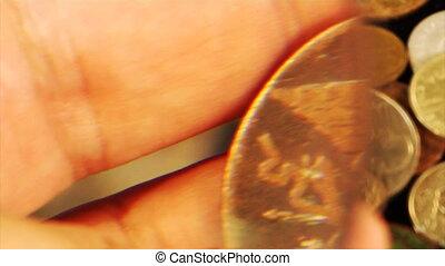 examining an old coin - close-up view examining an old...
