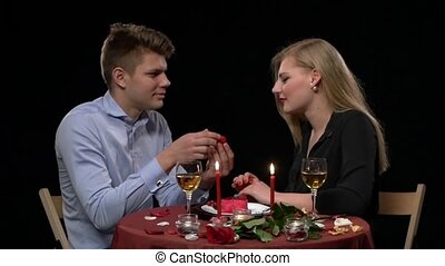 Close up of romantic dinner table with kissing young couple in bkack background. Slow motion