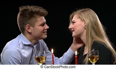 Close up of romantic dinner table with kissing young couple in bkack background. Close up. Slow motion