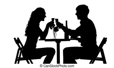 Romantic couple having dinner, clinking glasses. silhouette...