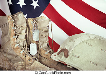 Old combat boots, dog tags, and helmet with American flag in...