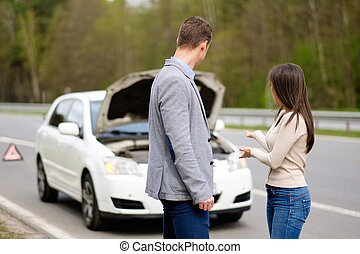 Couple near broken car on a highway roadside