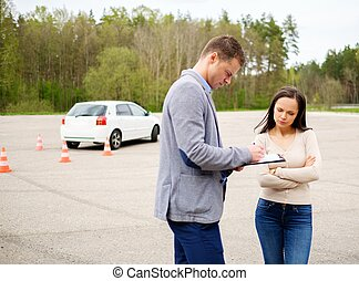 Driving instructor and woman student in examination area