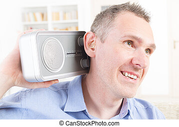 Hearing impaired man trying to listen radio