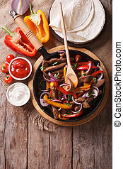 Mexican fajitas on a table, rustic style vertical top view -...