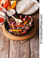 Mexican fajitas and ingredients vertical view above, rustic...