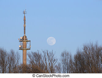Radio Tower With Moon - Radio tower and moon on a blue sky.