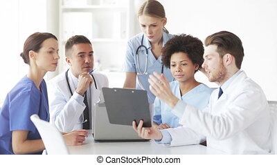 group of doctors with clipboard talking at clinic -...