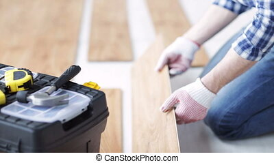 close up of man installing wood flooring - repair, building,...