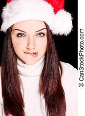 Girl biting her lip wearing Santa hat - A flirtatious young...