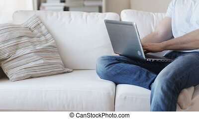 close up of man typing on laptop at home