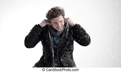 Handsome young man in winter cloth with snow on background