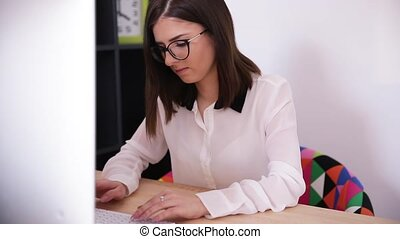Businesswoman typing on keyboard - Young businesswoman...