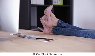 female legs on the table in office - Closeup image of a...