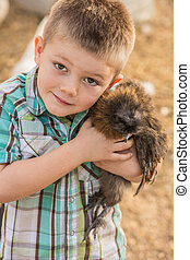 Boy Hugging Pet Chicken - Smiling boy outside hugs his pet...