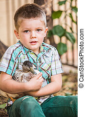 Pet Duck and Little Boy - Cute child in green holding his...