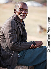 senior African man - old African resting on a stone, blurred...