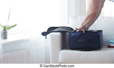 close up of man packing clothes into travel bag - trip,...
