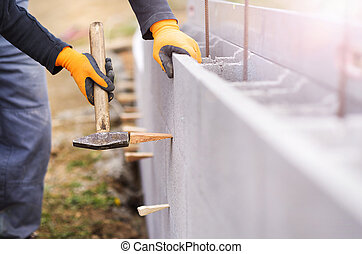 Man building a house - Bricklayer putting down another row...