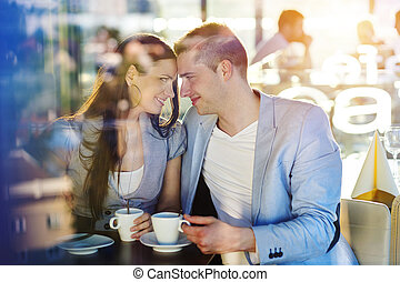 Beautiful young couple drinking coffee in cafe