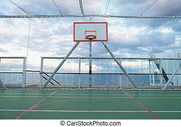 Netted Basketball Court - Basketball court and hoop with a...