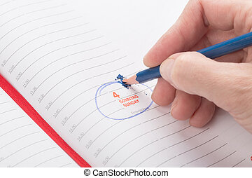female hand breaks a lead pencil on a date in the calendar