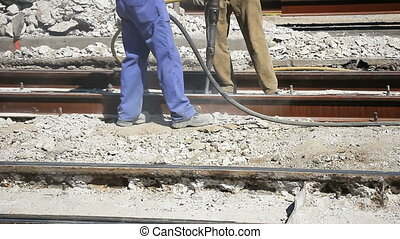 Two Workers with pneumatic hammer drill equipment breaking...