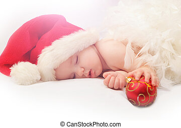 Small boy sleeping in a New Years cap - sleeping baby Santa...
