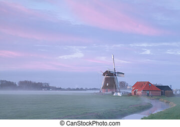 old windmill in sunrise fog by river